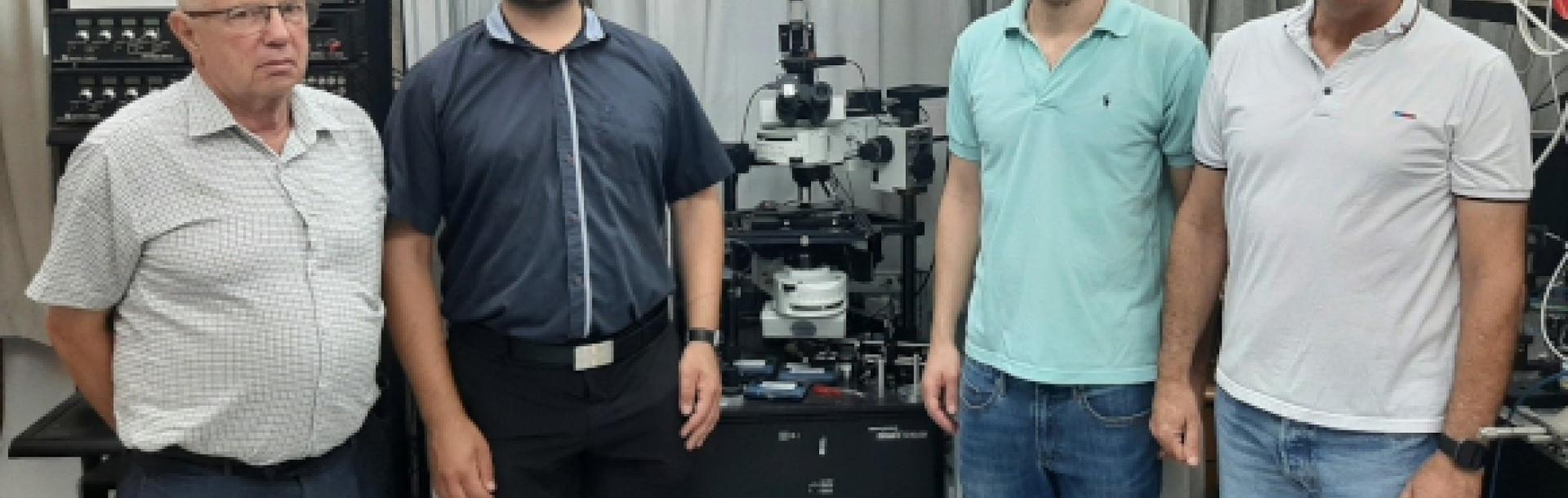 מימין לשמאל: פרופ' עדי אריה, הדוקטורנטים דרור ויסמן וגאורגי גרי רוזנמן ופרופ' לב שמר. במרכז - מיקרוסקופ אופטי סורק לשדה הקרוב באמצעותו בוצעו המדידות של הגלים הפלזמוניים